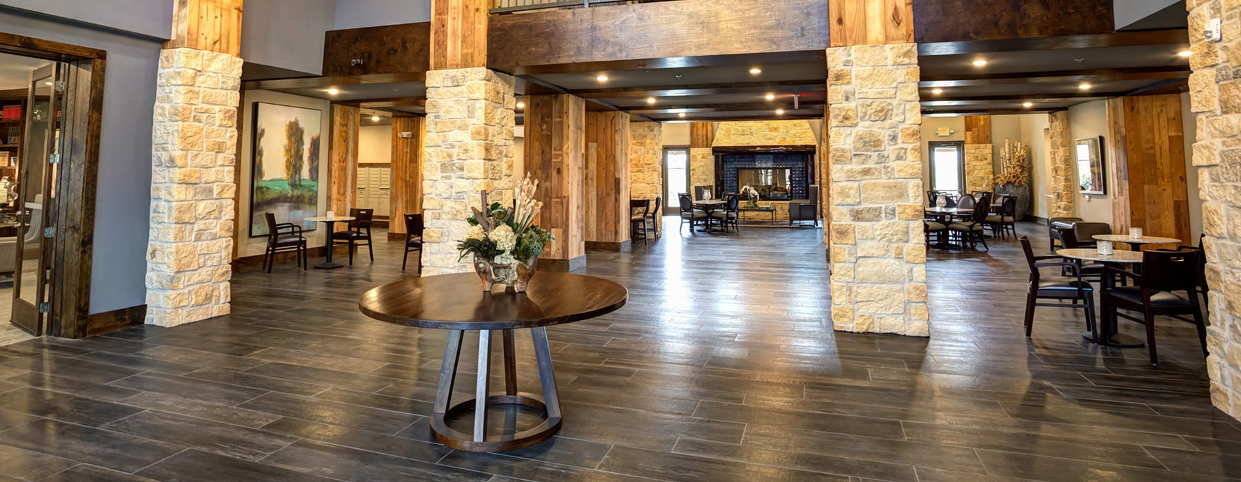 residents lobby with hardwood floors, large pillars, and tall ceilings